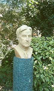 Outdoor bust of middle aged man with good head of hair, against a garden background
