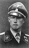 A black-and-white photograph of a man wearing a military uniform, peaked cap and a neck order in shape of an Iron Cross. His cap has an emblem in shape of a human skull and crossed bones. A large scar on his chin is visible.