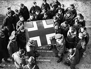 Roland Beamont - Pilots and ground crew gather around the fuselage Balkenkreuz from No 87 Squadron's first kill, a Heinkel 111 on 2 November 1939. Watching on the right is Pilot Officer Roland Beamont (in flying helmet, with initials on his flying jacket)