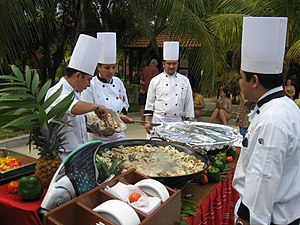 Chefs preparing a seafood paella in Playa del ...