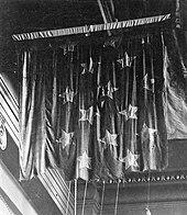 Una foto en blanco y negro de una bandera de batalla-desgastado suspendida del techo de un museo