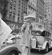 "A man in a big-city street between parked cars holds a folded newspaper up in front of his face with one hand, and carries other copies with his other hand. The man's suit and the cars' styles are from the 1930s. The newspaper masthead is ""Social Just..."" and the huge lead headline reads ""ANNIVERSARY OF VERSAILLES ... THREAT TO U.S. PEACE""."