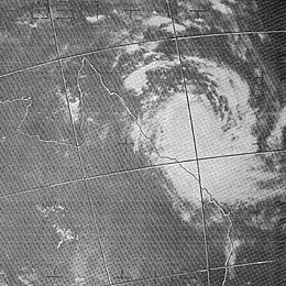 Satellite image of a tropical cyclone near the northeastern coast of Australia. Curved rainbands are shown but no eye is visible.