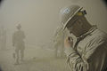 Defense.gov News Photo 100504-N-0475R-766 - U.S. Navy Petty Officer 2nd Class Eric Clark a Seabee attached to Naval Mobile Construction Battalion 5 is caught in a sandstorm at Camp.jpg