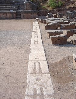 This starting line at the Delphi stadium used for the Pythian Games at Delphi, Greece has a design representative of that of many ancient Greek stadiums: stones with two lines in which the athletes nudged their toes, and round holes in which posts could be erected to support the start signalling mechanism.