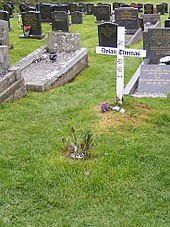 Uma cruz branca simples gravado com uma mensagem memorial de Thomas está em uma jarda grave