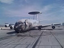 Jet aircraft resting on ramp with an nose-down attitude. The nose is black, sustained during a fire. On top of it is a circular radar.