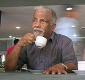Old man drinking from a white cup in his hand.