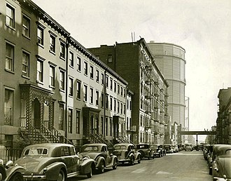 Stuyvesant Town–Peter Cooper Village - East 20th Street looking east in the direction of First Avenue in 1938. This picture shows two of the huge gas holders that gave the area the name Gas House District; the block in the foreground did not become part of the Stuyvesant Town–Peter Cooper Village complex, but the area on the east side of First Avenue, where the tanks are, did. (Photo by Berenice Abbott)
