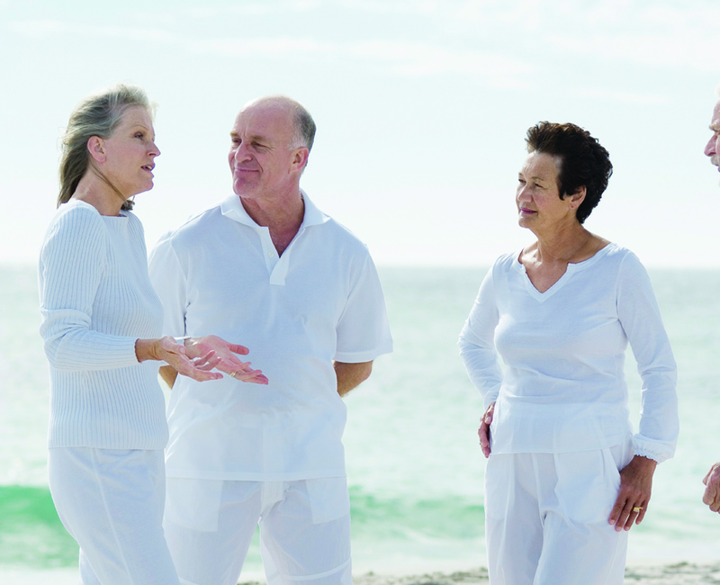 Three eldery people stand on a beach, in conversation.