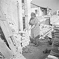 Emigrantenvrouw, een advocate uit Roemenie, bikt bakstenen temidden van een door, Bestanddeelnr 255-1203.jpg