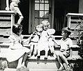 Enfants jouant avec des poupées devant une maison à Rivberbend, Alma (Québec).jpg