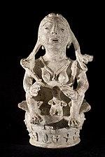 statuette en pierre représentant un personnage féminin assis abritant de ses mains un petit personnage situé entre ses jambes