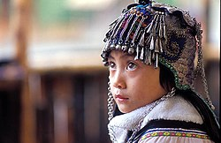 An ethnic Hani girl with a typical Hani headgear for children. Near Yuanyang, Yunnan Province, China