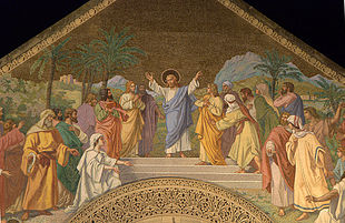 Jesus, with His arms stretched out, welcomes people who are coming towards him from both sides. A Middle eastern landscape is behind the group.