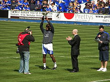 Four men standing on a grass football pitch. The man second from left, wearing a grey top, white shorts and white socks, is holding a trophy above his head. Spectators wearing blue or black tops are visible in the background.
