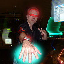 Stylized image of Frank Klepacki at his office wearing sunglasses and sticking his hand to the camera, red and green neon glow effects around his hair, hand, and sunglasses