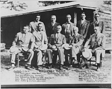 Black and white photograph of several political figures seated in front of a rustic building, FDR in the center of the group.