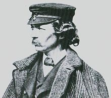 A man in oblique profile with a mustache is wearing a coat and hat looking toward the left.