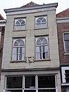 foto van Huis met rood schilddak en gebosseerd grijsgepleisterde lijstgevel, ramen met waaierzwikken; gevelsteen in de vorm van een cartouche waarin een pauw. Winkel