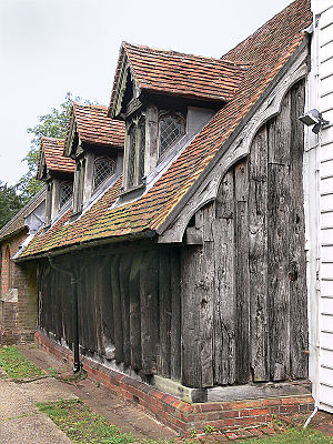 """Greensted Church - The north wall and part of the west wall of the nave; the notch, low down on the 7th trunk along from the corner, may either be a """"leper's squint"""", or a Saxon window."""