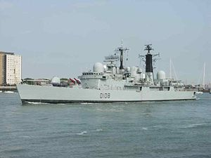 Grey warship with black towers and red missiles on its bow, city buildings are in the background.