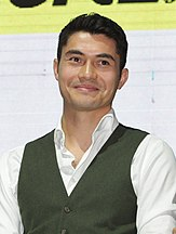Henry Golding smiles, facing forward