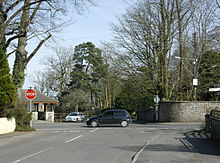 Street scene. Road junction with red stop sign. Two cars. The sides of the roads are stone walls with large trees showing above them.