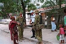 Fotografía de miembros australianos de las Fuerzas Internacionales de Timor Oriental (INTERFET), hablando con un ciudadano en Dili, Timor Oriental en 2000