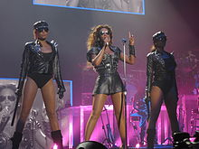 Three women are standing in front of many musicians and a big television screen. From left to right, the first and third women are wearing a black suit. It consist of a cap, glasses, a jacket, a leotard, gloves and boots. They hold a tonfa with their right hand. The second woman is wearing a gray dress (styled like a Roman war-suit) and black glasses. She raises her left hand and points with her index finger. She holds a microphone with her other hand.