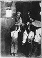 Indianapolis Newsboys buying brass checks in a newspaper office. These checks cost at the rate of one-half the... - NARA - 523074.tif