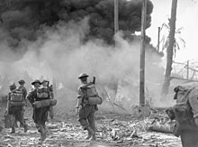 Soldiers in combat equipment with helmets and rifles advance towards a thick cloud of smoke
