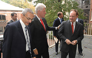 Three older, white men in suits and ties stand on a stone balcony, with trees and brick buildings behind them.