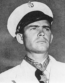 Black and white photo of male individual in chief petty officer dress whites wearing the Navy Medal of Honor