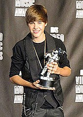 Justin Bieber in 2010 at the VMAs red carpet holding an award.