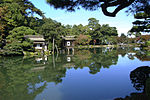 A stone lantern next to a tree in front of a pond. Beyond the lake there is a small wooden house built on poles above the water.