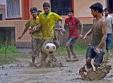 several young men playing association football in a muddy field in the rain