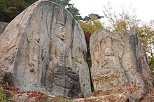 Five Buddhas carved into two natural rocks.
