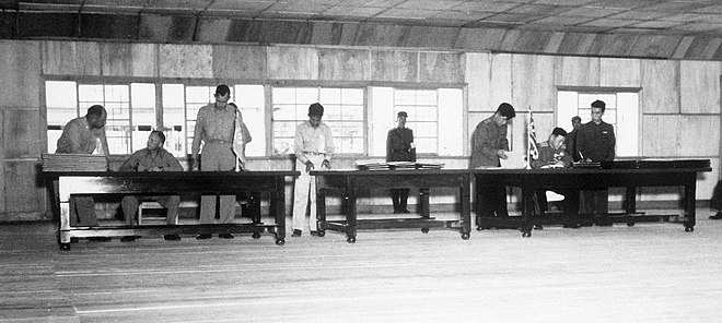 Delegates sign the Korean Armistice Agreement in P'anmunjom. Korean War armistice agreement 1953.jpg