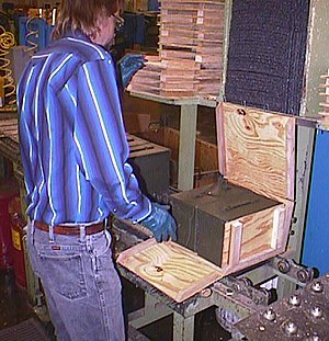 Lake City Army Ammunition Plant - A worker at Lake City Army Ammunition Plant packs two cans of newly manufactured 5.56×45mm NATO ammunition into a wirebound crate. (ca. 1998)