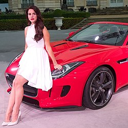 A brunette female wearing a white dress poses on a red luxury car.