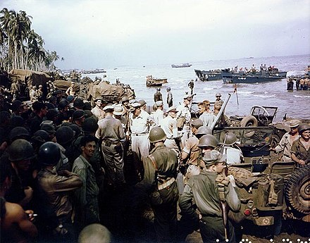 General Douglas MacArthur (center), accompanied by Lieutenant Generals George C. Kenney and Richard K. Sutherland and Major General Verne D. Mudge (Commanding General, First Cavalry Division), inspecting the beachhead on Leyte Island, 20 October 1944 with a crowd of onlookers. Leyte beachhead.jpg