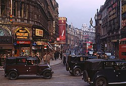 """A busy 1949 city scene in London, England, with black vintage vehicles, red London buses and many pedestrians. Buildings advertise «Wills's Gold Flake Cigarettes» and «Craven A» cigarettes."