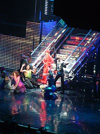 A woman wearing a red ensemble, standing in front of a metallic staircase around a group of dancers.