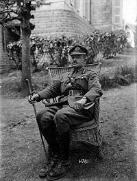 A black and white photograph of a man wearing military uniform seated on a garden chair on a lawn