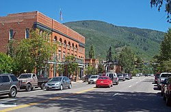 A wide undivided street with cars traveling in both directions going past a large brick building. In the rear is a forested mountain