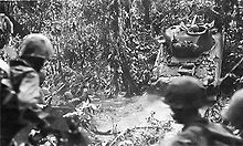In the foreground Marines watch as a light tank climbs up the bank of creek in a jungle setting.