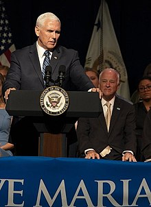Mike Pence stands at a podium in the foreground; Towey is seated behind him, looking on.