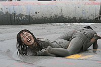 Photograph of two women wrestling and covered in mud