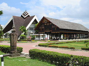 Rumoh Aceh - Aceh Museum featuring the traditional Rumoh Aceh, in the background is a modern interpretation of the Cakra Donya roof.